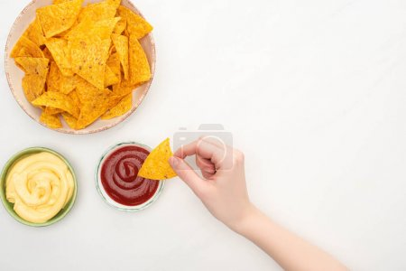 Photo for Cropped view of woman eating corn nachos with cheese sauce and ketchup on white background - Royalty Free Image
