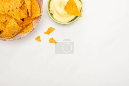 Photo for Top view of corn nachos with cheese sauce on white background - Royalty Free Image