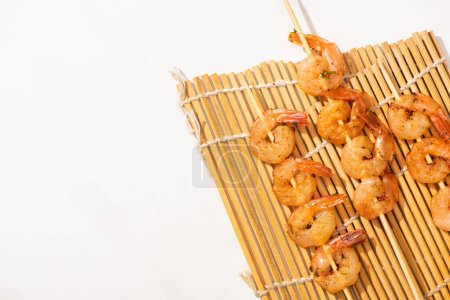 Photo for Top view of prawns on skewers on bamboo mat on white background - Royalty Free Image