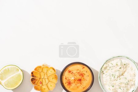 top view of garlic, lime and sauces on white background