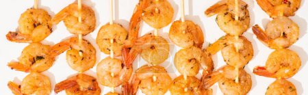 top view of delicious fried prawns on skewers on white background, panoramic crop
