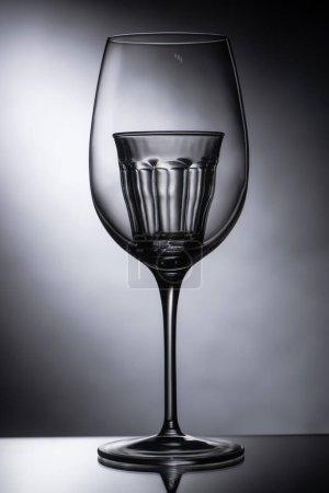 empty shot glass in wine glass on dark background