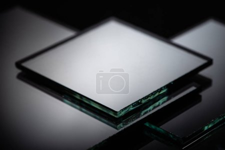 close up view of square mirror pieces in stack on black