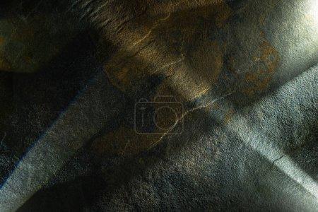 Photo pour Prisme léger avec poutres sur fond de texture de pierre sombre - image libre de droit