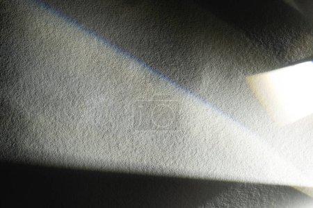 Foto de Prisma claro con vigas en fondo texturado oscuro - Imagen libre de derechos