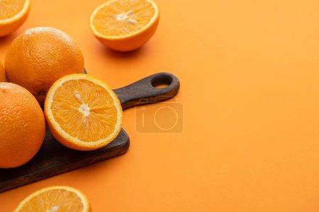 Photo pour Mûr délicieux couper et des oranges entières sur planche à découper en bois sur fond coloré - image libre de droit