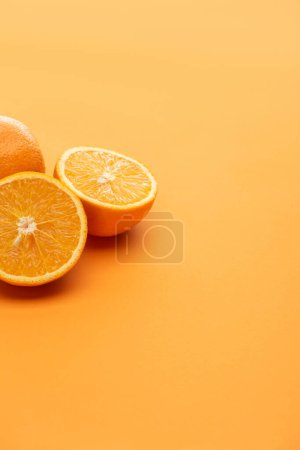 Photo for Ripe delicious cut and whole oranges on colorful background - Royalty Free Image