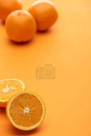 Foto de Foco selectivo de naranjas maduras jugosas enteras y cortadas sobre fondo colorido - Imagen libre de derechos