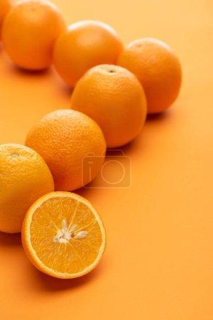 Photo pour Mise au point sélective d'oranges juteuses entières et coupées sur fond coloré - image libre de droit