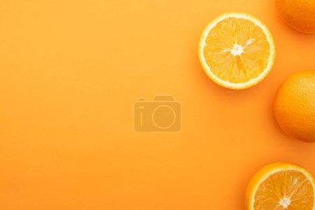 Photo pour Vue de dessus des oranges entières juteuses et des tranches sur fond coloré - image libre de droit