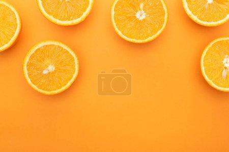 Photo pour Vue du haut de tranches d'orange juteuses et mûres sur fond coloré avec espace de reproduction - image libre de droit