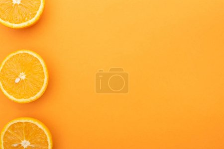 top view of ripe juicy orange slices on colorful background with copy space