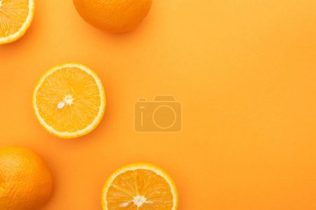 Photo for Top view of ripe juicy whole oranges and slices on colorful background - Royalty Free Image