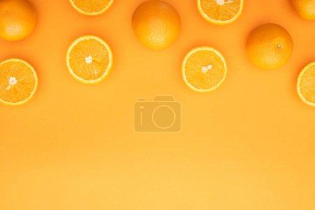 Photo pour Vue de dessus des oranges entières juteuses mûres et des tranches sur fond coloré - image libre de droit