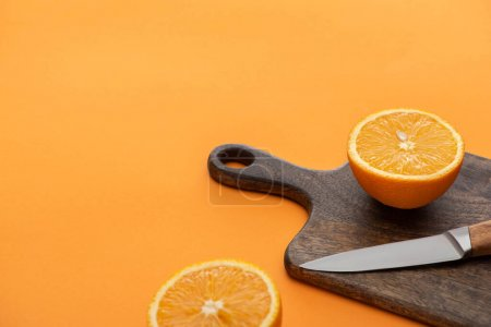 fresh juicy orange halves on cutting board with knife on colorful background