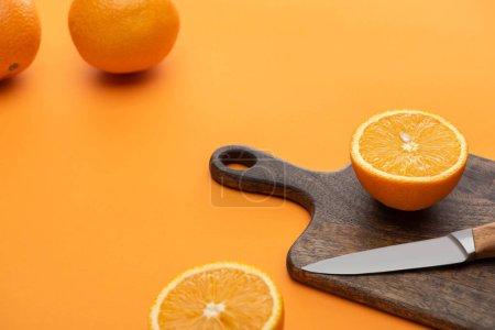 Photo pour Frais juteux oranges entières et coupées sur planche à découper avec couteau sur fond coloré - image libre de droit