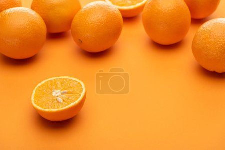 Photo for Ripe juicy whole and cut oranges on colorful background - Royalty Free Image