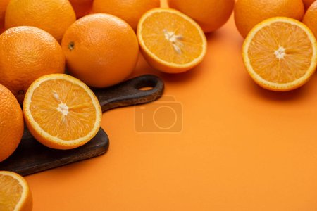 fresh juicy oranges on cutting board on colorful background