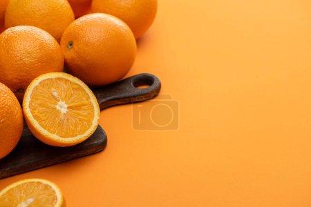 Photo pour Oranges fraîches juteuses sur planche à découper sur fond coloré - image libre de droit