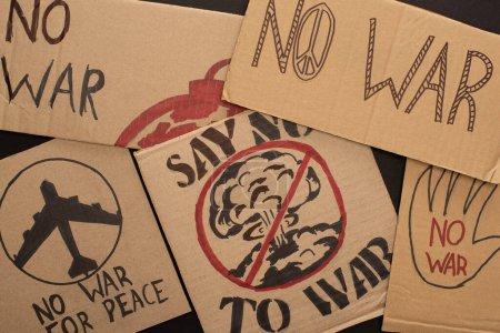 Photo pour Vue du dessus des plaques en carton sans lettrage de guerre et dessins sur fond noir - image libre de droit