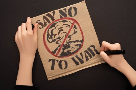 Photo for Cropped view of woman drawing placard with say no to war lettering on black background - Royalty Free Image