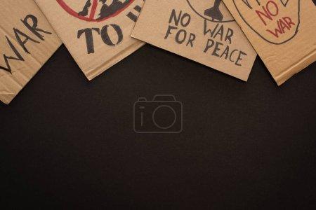 Photo pour Vue du dessus des plaques en carton sans lettrage de guerre sur fond noir - image libre de droit