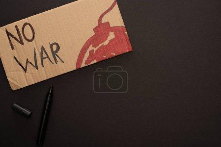 Photo pour Vue du dessus du marqueur et de la plaque en carton sans lettrage de guerre et sans bombe sur fond noir - image libre de droit