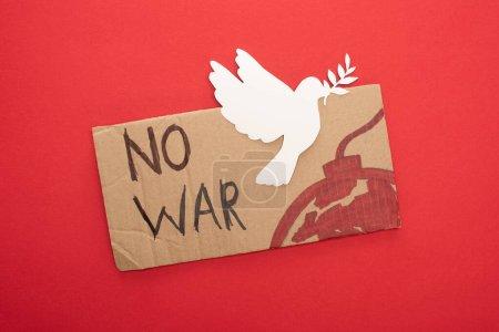 Photo pour Vue du dessus de la plaque en carton sans lettrage de guerre et bombe avec colombe en papier blanc sur fond rouge - image libre de droit