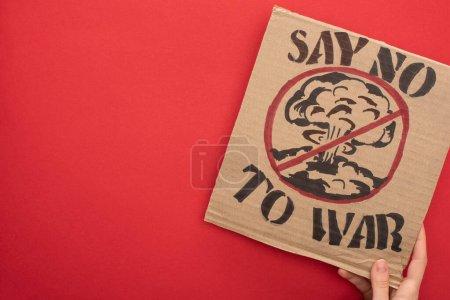 vista parcial de la mujer sosteniendo cartel de cartón con decir no a la guerra letras de guerra y explosión en señal de stop sobre fondo rojo