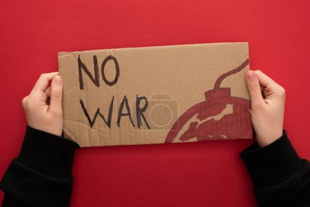 Photo for Cropped view of woman holding cardboard placard with no war lettering and bomb on red background - Royalty Free Image