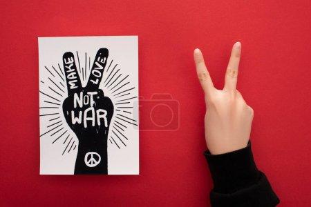 Photo pour Vue recadrée de la femme montrant signe de paix près de dessin avec faire l'amour pas lettrage de guerre et signe de paix sur fond rouge - image libre de droit
