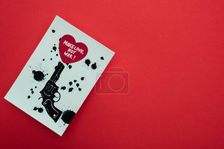 Photo pour Top view of white paper with drawn black revolver and heart with make love not war lettering on red background - image libre de droit