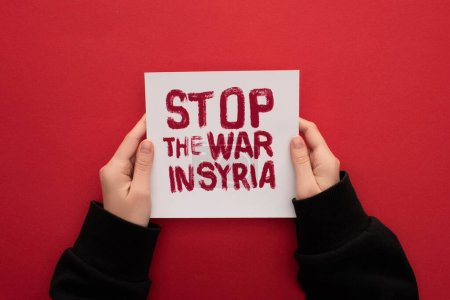 Photo for Partial view of woman holding white placard with stop war in Syria lettering on red background - Royalty Free Image