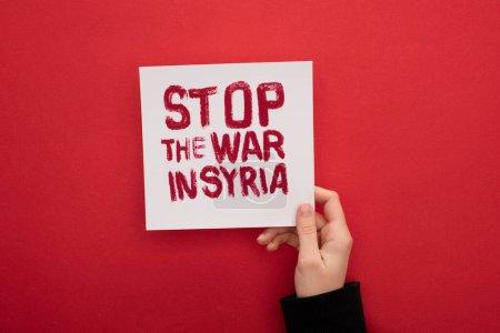 Photo pour Vue partielle de la femme tenant une pancarte blanche avec inscription stop war in Syria sur fond rouge - image libre de droit