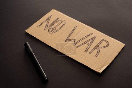 Photo pour Plaque en carton sans lettrage de guerre et signe de paix près du marqueur sur fond noir - image libre de droit