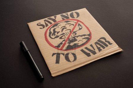 rotulador cerca de cartel de cartón con decir no a las letras de guerra y explosión en señal de stop sobre fondo negro