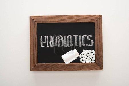 Photo pour Vue du haut du tableau avec des probiotiques lettrage avec des pilules et récipient sur fond blanc - image libre de droit