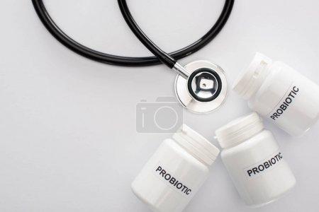 Photo pour Vue de dessus des récipients avec lettrage probiotique près du stéthoscope sur fond blanc - image libre de droit