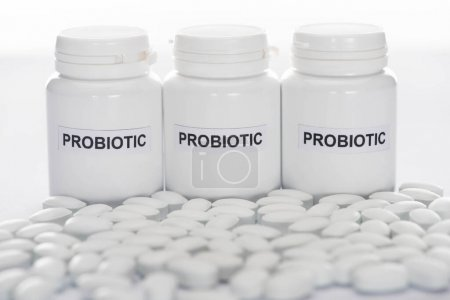 Photo for Selective focus of probiotic containers near pills on white background - Royalty Free Image