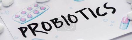 Photo pour Mise au point sélective du dessin avec des probiotiques lettrage près de pilules sur fond blanc, plan panoramique - image libre de droit