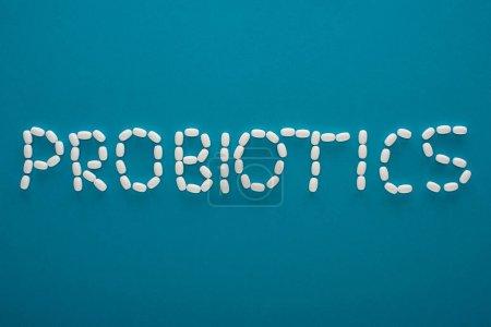 Photo pour Vue du dessus des probiotiques lettrage en pilules sur fond bleu - image libre de droit