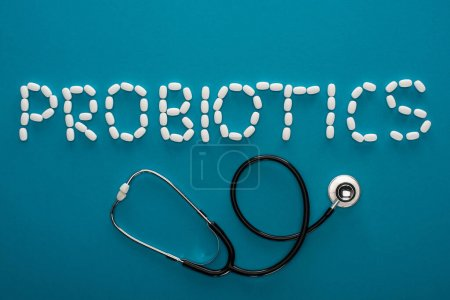 Photo for Top view of probiotics lettering made of pills and stethoscope on blue background - Royalty Free Image