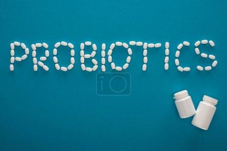 Photo pour Vue du dessus des probiotiques lettrage en pilules et récipients sur fond bleu - image libre de droit