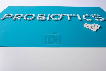 probiotics lettering and heart made of pills on blue and white background