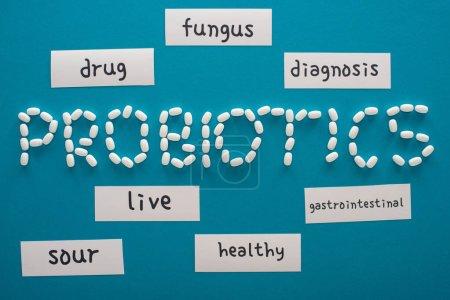 Photo pour Vue du dessus des probiotiques lettrage fait de pilules près de cartes de papier avec des mots sur fond bleu - image libre de droit