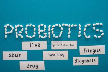 vue du dessus des probiotiques lettrage fait de pilules près de cartes de papier avec des mots sur fond bleu
