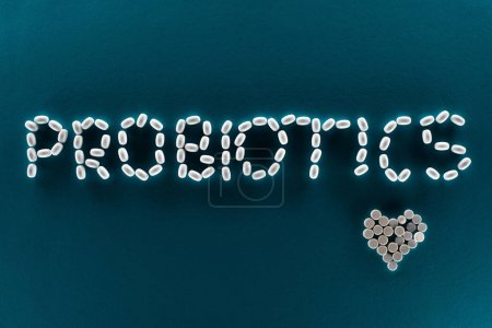 top view of probiotics lettering made of pills on blue background