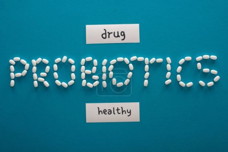 Photo for Top view of probiotics lettering made of pills near paper cards with healthy and drug words on blue background - Royalty Free Image