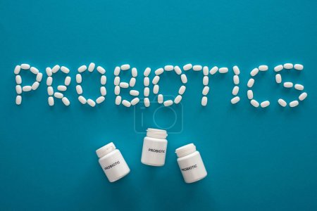 Photo for Top view of probiotics lettering made of pills and containers on blue background - Royalty Free Image