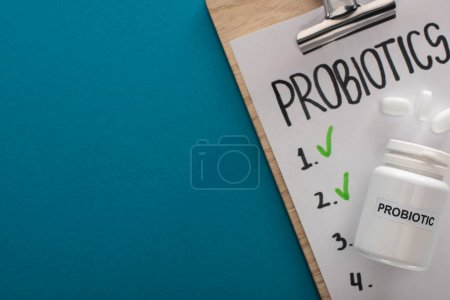Photo for Top view of clipboard with probiotics empty list near container with pills on blue background - Royalty Free Image